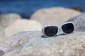 Sunglasses with colorful floral eyeglass frame lies on a rock on the coast — Stock Photo