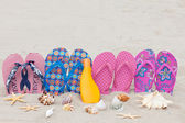 Four pairs bath slippers in a row stuck in the sand beach — Stock Photo
