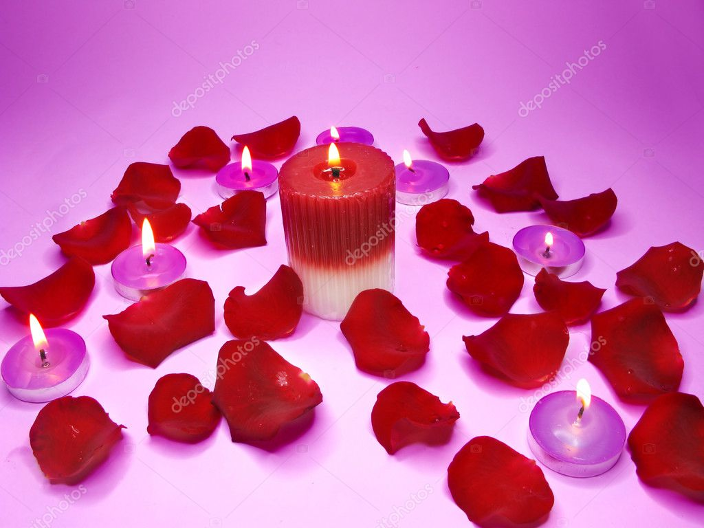 Spa lit candles among damask rose petals — Stock Photo #10909191