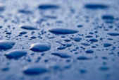 Water drops on blue surface — Stock Photo