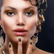 Foto de Stock  : Golden Makeup and Jewelry. Fashion Model Portrait