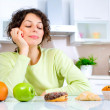 Stock Photo: Diet. Beautiful Young Womchoosing between Fruits and Sweets