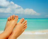 Vacation Concept. Woman's Bare Feet over Sea background — Stock Photo