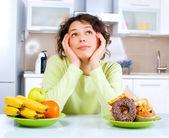Belle jeune femme en choisissant entre fruits et bonbons — Photo