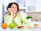 диета. красивая молодая женщина, выбирая между фрукты и сладости — Стоковое фото