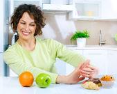 красивая молодая женщина, выбирая между фрукты и сладости — Стоковое фото