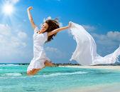 Hermosa chica con bufanda blanca saltando en la playa — Foto de Stock