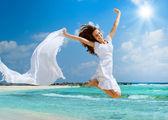 красивая девушка с белый шарф, прыжки на пляже — Стоковое фото