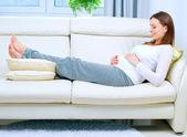 беременная женщина на диване у себя дома — Стоковое фото
