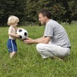 Foto Stock: Father and his son with their ball in the park