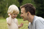 Happy father and the son listen to music — Stockfoto