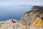 Girl sitting on precipice above sea — Stock Photo