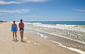Happy man and woman couple walking on beach — Stock Photo