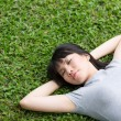 Asian woman lying sleeping on grass. — Stock Photo