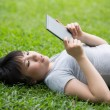 Chinese woman is reading her e-book reader — Stock Photo