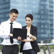 Asian Business man and woman using a Laptop outside — Stock Photo