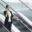Business woman using a mobile phone on an Escalator — Stock Photo