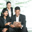 Stock Photo: Indian Business looking at a digital tablet.