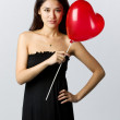 Woman holding a heart shaped balloon for Valentines Day - Stock Photo