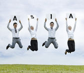 Asian man & woman jumping holding with a sign — Stock Photo