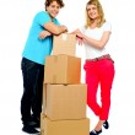 Teenager couple posing beside cardboard boxes — Stock Photo