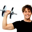 Powerful muscular young man lifting weight — Stock Photo #10776280