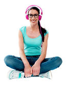 Teenager sitting on floor and listening music — Stock Photo