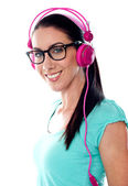 Pretty girl tuned into listening music via headphones — Stock Photo