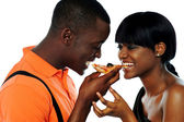Young couple sharing a slice of pizza — Stock Photo