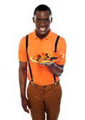 Smiling young african boy offering pizza — Stock Photo