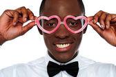 Smiling man wearing heart shaped eye-wear — Stock Photo
