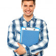 Young man holding clipboard and notepad — Stock Photo