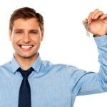 Portrait of smiling businessman holding keys — Stock Photo