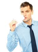 Young businessman smoking cigarette — Stock Photo
