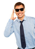 Guy wearing sunglasses and listening to music — Stock Photo