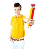 Stylish boy showing two large pencils — Stock Photo