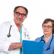 Senior doctors reading medical report — Stock Photo #11421773