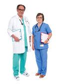 Senior male doctor posing with female nurse — Stock Photo