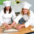 Stock Photo: Female chef arranging prepared dough