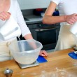 Females hand pouring water into flour bowl - Stock fotografie