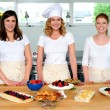 Team of confident chefs presenting snacks — Stock Photo