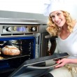 Royalty-Free Stock Photo: Pretty baker opening an oven door