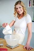 Sorridente donna versando acqua nella ciotola di farina — Foto Stock