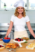 Female chef posing in uniform inside kitchen — Stock Photo