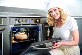 Pretty baker opening an oven door — Stockfoto