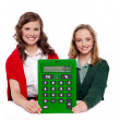 Girls showing big green calculator to camera — Stock Photo
