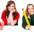 Beautiful schoolgirls posing with big pencil — Stock Photo