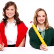 Female students writing with big pencil — Stock Photo