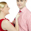 Glamorous woman pulling man by his tie — Stock Photo #11781956