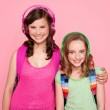 Sisters standing together and enjoying music — Stock Photo